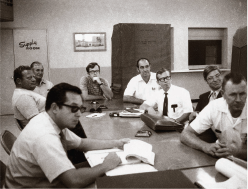 black and white photo of men in a work meeting and sitting around a table