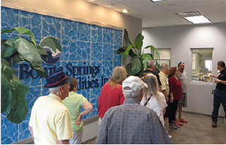 Visitors stand in the lobby of the water plant which has a blue wall and fake palm trees.