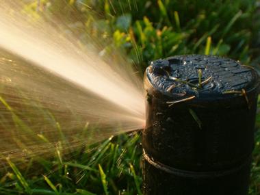 a sprinkler waters grass using reclaimed water
