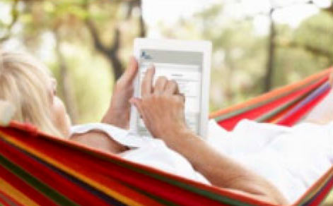 a lady in a hammock uses a tablet to pay her water bill online